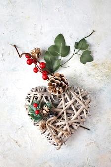 Foto vertical de um coração de madeira decorativo com tema natalino em uma superfície de mármore branco