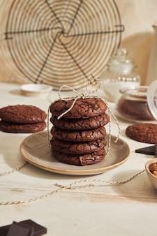 Foto vertical de um delicioso biscoito de chocolate com calda de chocolate com ingredientes em uma mesa branca