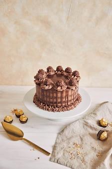 Foto vertical de um delicioso bolo de chocolate em um prato ao lado de alguns pedaços de chocolate