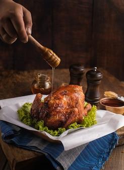 Foto vertical de um delicioso frango assado decorado com vegetais e mel em uma mesa