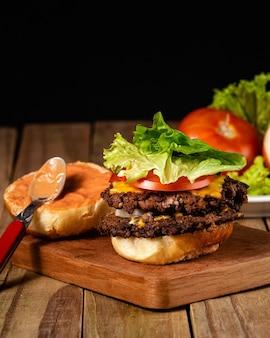 Foto vertical de um delicioso hambúrguer com o molho do pão em uma placa de madeira