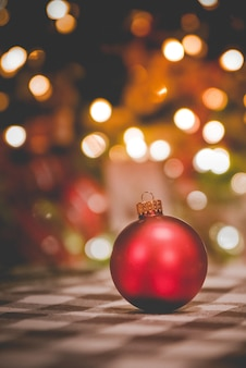 Foto vertical de um enfeite de natal sob as luzes desfocadas
