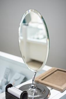 Foto vertical de um espelho de prata em uma cômoda