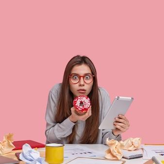 Foto vertical de um estudante universitário assustado olhando através dos óculos, segurando uma rosquinha saborosa, carregando um touchpad atualizado, com muitos documentos na mesa