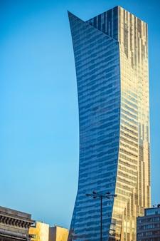 Foto vertical de um grande arranha-céu sob o céu azul