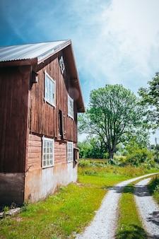 Foto vertical de um grande celeiro de madeira no campo