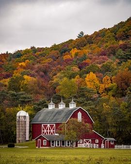Foto vertical de um grande celeiro perto de uma colina com árvores coloridas de outono
