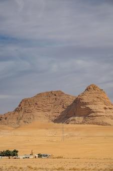 Foto vertical de um grande penhasco em um deserto sob um céu nublado