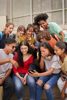 Foto vertical de um grupo multiétnico de estudantes usando telefone celular e adolescentes rindo usando um sm ...