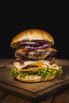 Foto vertical de um hambúrguer delicioso em uma bandeja de madeira
