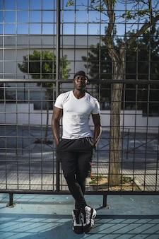 Foto vertical de um homem afro-americano com uma camisa branca encostado em uma cerca