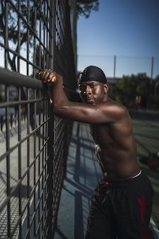 Foto vertical de um homem afro-americano seminu encostado na cerca na quadra de basquete