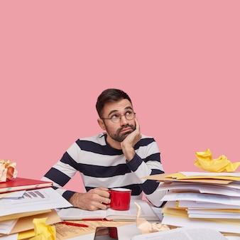 Foto vertical de um homem barbudo pensativo mantendo a mão sob o queixo, vestindo um suéter listrado e bebendo café