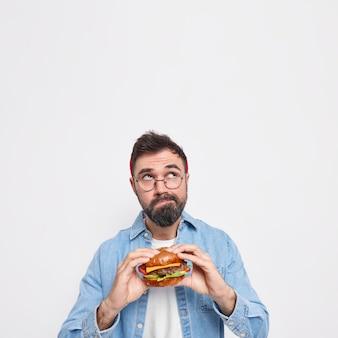 Foto vertical de um homem barbudo pensativo segurando um hambúrguer apetitoso focado acima, pensando profundamente sobre algo