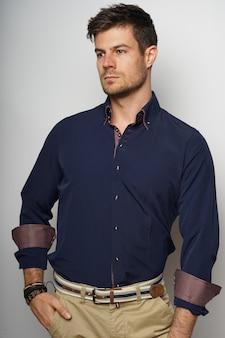 Foto vertical de um homem bem-sucedido em pé com a mão no bolso