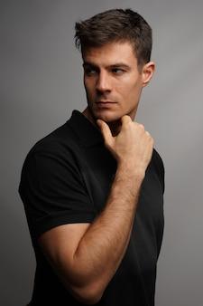 Foto vertical de um homem bonito segurando seu queixo com um braço contra uma parede cinza