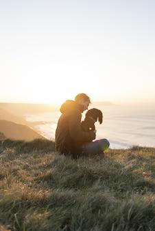Foto vertical de um homem branco apreciando o pôr do sol no oceano com seu cachorro