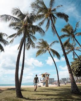 Foto vertical de um homem caminhando em uma praia coberta de palmeiras enquanto aproveita o dia ensolarado