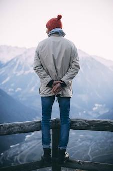 Foto vertical de um homem com um chapéu vermelho e em pé sobre uma cerca de madeira com montanhas