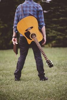 Foto vertical de um homem com um violão e um livro na mão em pé na grama