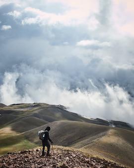 Foto vertical de um homem de pé em uma montanha com um céu nublado ao fundo