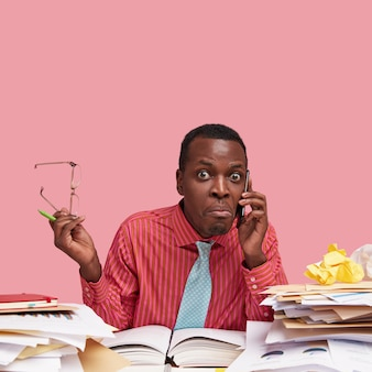 Foto vertical de um homem de pele escura surpreso conversando ao telefone, parece perplexo, vestido com roupas formais, segura os óculos nas mãos