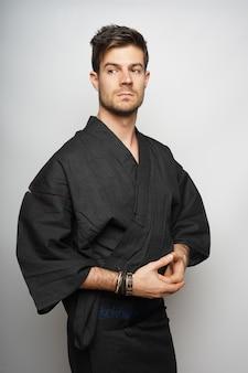 Foto vertical de um homem em pé concentrado em seu quimono de estilo japonês
