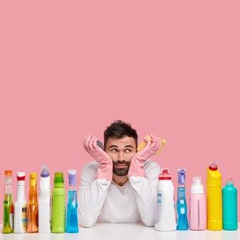 Foto vertical de um homem frustrado e chateado com a barba por fazer, usa roupas brancas casuais e luvas de proteção de borracha, usa detergentes