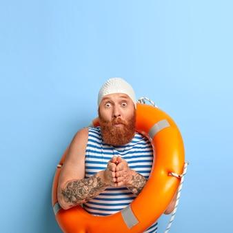 Foto vertical de um homem ruivo surpreso com barba espessa, mantém as palmas das mãos juntas, pronto para mergulhar, usa touca de borracha de proteção, colete de marinheiro, olhos saltados