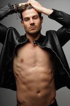 Foto vertical de um homem sexy sem camisa em uma jaqueta de couro posando sobre uma parede cinza
