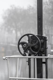 Foto vertical de um instrumento de metal com um pequeno volante