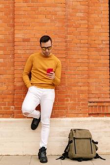 Foto vertical de um jovem bonito com óculos escuros e seu smartphone na rua tomando um café. roupas amarelas e primavera. conceito de estilo de vida.