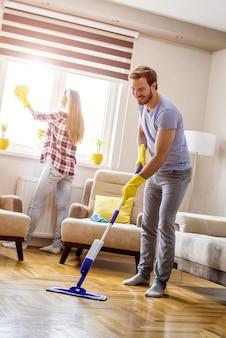 Foto vertical de um jovem casal caucasiano limpando a casa e se divertindo
