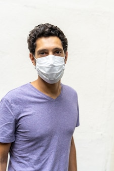 Foto vertical de um jovem com uma máscara no rosto para proteger