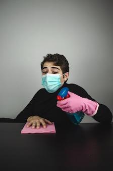 Foto vertical de um jovem do sexo masculino com uma máscara médica, limpando e desinfetando uma mesa