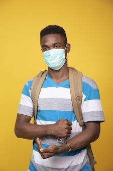 Foto vertical de um jovem do sexo masculino usando uma máscara e um desinfetante para as mãos