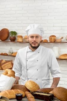 Foto vertical de um jovem e bonito padeiro profissional posando em sua loja cercado por vários tipos de pão