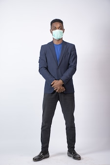 Foto vertical de um jovem empresário negro vestindo um terno e também uma máscara facial, em pé com confiança