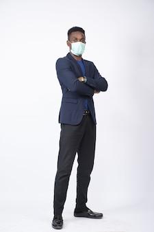 Foto vertical de um jovem negro vestindo um terno e uma máscara facial em pé com confiança