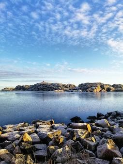 Foto vertical de um lago cercado por formações rochosas em stavern, noruega