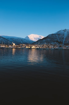 Foto vertical de um lago rodeado por montanhas cobertas de neve em tromso, noruega