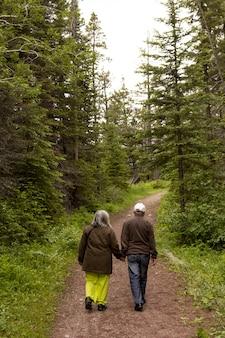 Foto vertical de um lindo casal de idosos caminhando na floresta