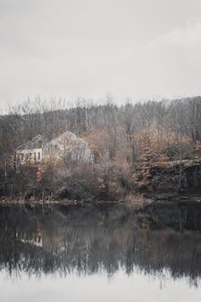 Foto vertical de um lindo lago cercado por florestas de colinas e uma casa inacabada