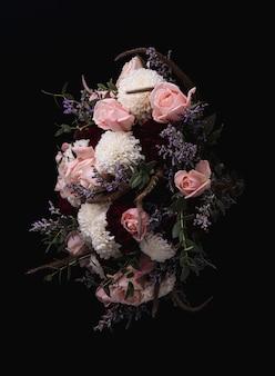 Foto vertical de um luxuoso buquê de rosas cor de rosa e dálias brancas e vermelhas em um fundo preto