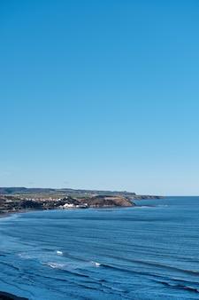 Foto vertical de um mar azul e um céu claro durante o dia