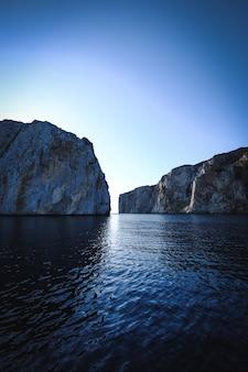 Foto vertical de um mar com falésias ao fundo