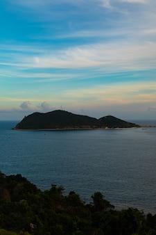 Foto vertical de um mar com uma ilha à distância no vietnã