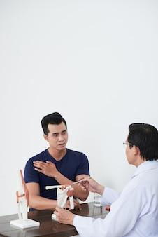 Foto vertical de um médico irreconhecível, vestindo jaleco branco, sentado na mesa na frente de um jovem segurando um modelo de articulação do ombro, discutindo a necessidade de fisioterapia