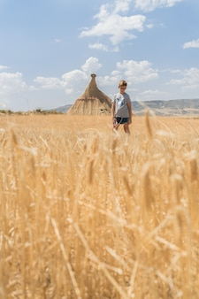 Foto vertical de um menino em um campo de trigo