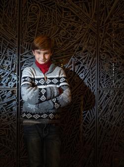 Foto vertical de um menino fofo com as mãos cruzadas em frente a uma parede